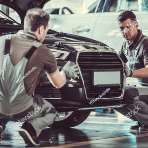 stock-photo-handsome-mechanics-in-uniform-are-examining-car-while-working-in-auto-service-618009977-500